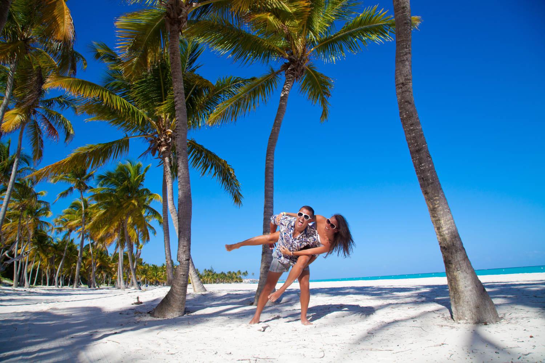 זוג נהנה מחוף לבן ומקסים באיים הקריביים עם דקלי קוקוס
